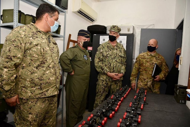 .S. Southern Command's commander, Navy Adm. Craig Faller, is briefed on helicopter parts and equipment donated by the United States to the Uruguayan military.