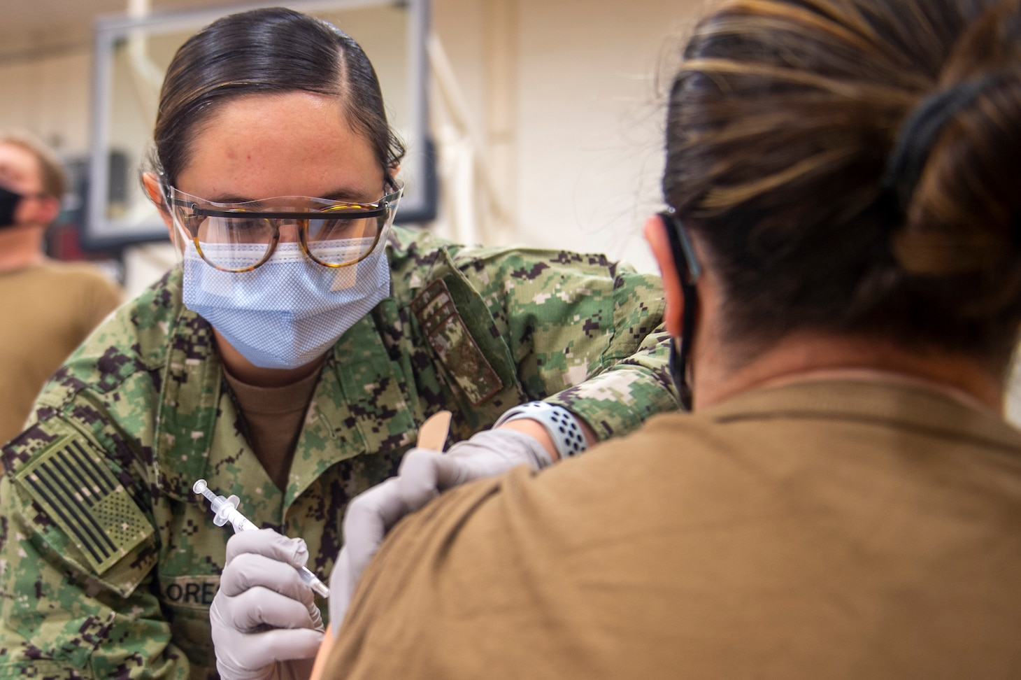 A hospital corpsman administers the COVID-19 vaccine to a Sailor onboard Naval Air Station Oceana.