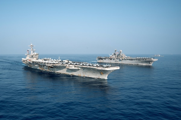 The Theodore Roosevelt Carrier Strike Group transits in formation with the Makin Island Amphibious Ready Group in the South China Sea, April 9, 2021.