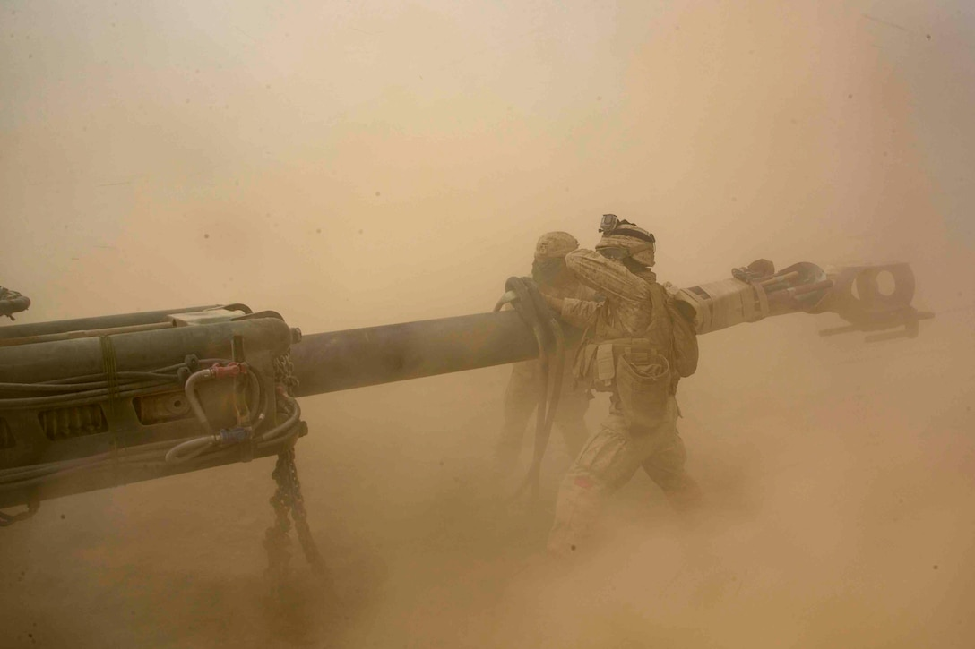 Two Marines stand on either side of a howitzer as dust surrounds.