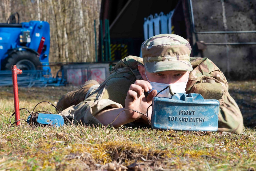 An airman lies on the ground while working on a mine.