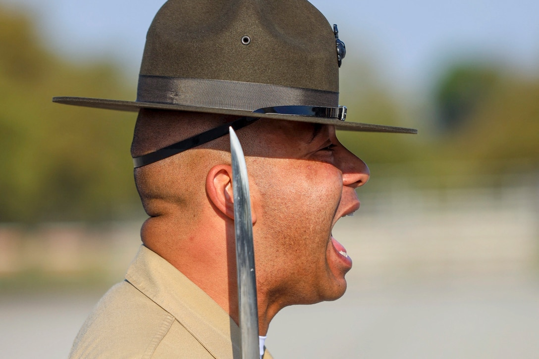A Marine yells while holding a sword next to his face.