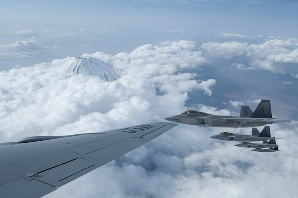 U.S Air Force Raptors from the 199th Fighter Squadron fly alongside a USAF KC-135 Stratotanker from the 909th Air Refueling Squadron during fifth-generation fighter training near Mount Fuji, Japan, April 1, 2021. The F-22 Raptors were operating out of Marine Corps Air Station Iwakuni, Japan, to support the U.S. Indo-Pacific Command's dynamic force employment concept.