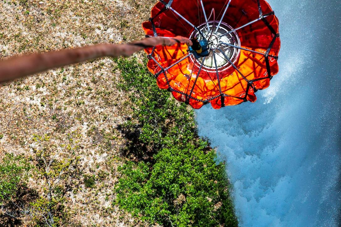 A water bucket hangs from an aircraft.