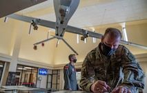 Maj. Gen. David Meyer signs a lithograph at Creech Air Force base inside the wing headquarters building.