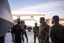 Maj. Gen. David Meyer speaks with 432nd Wing/432nd Air Expeditionary Wing Airmen beside an MQ-9 Reaper.