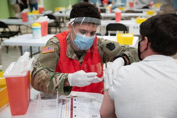 Spc. Isiah Bingham, a health care specialist with the Maryland Army National Guard's Headquarters and Headquarters Company, 1st Battalion, 175th Infantry Regiment, administers a COVID-19 vaccine at a mass vaccination site in Hagerstown, Maryland, March 26, 2021. The site was the sixth COVID-19 mass vaccination site set up in Maryland.
