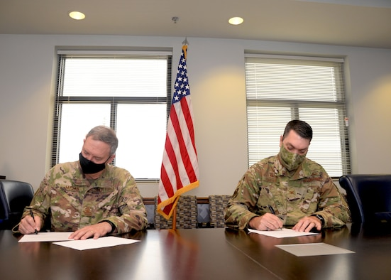 Col. Terry McClain, 433rd Airlift Wing commander, and Col. Rick Erredge, 960th Cyberspace Wing commander, sign copies of their respective versions of the 433rd AW and 960th CW Memorandum of Understanding, April 6, 2021, at Joint Base San Antonio-Lackland, Texas. (U.S. Air Force photo by Samantha Mathison)