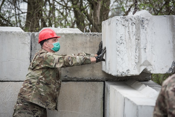 U.S. Air Force Staff Sgt. Peter Louden, a pavements and construction Airman with the 201st RED HORSE Squadron, Pennsylvania Air National Guard, guides a retaining wall block in place as it is lowered.