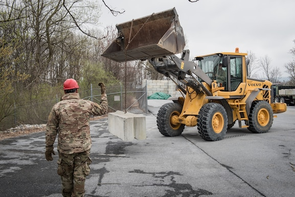 U.S. Air Force Senior Airman Randy Miller, a pavements and construction Airman with the 201st RED HORSE Squadron, Pennsylvania Air National Guard, ground guides an Airman operating a wheel loader.