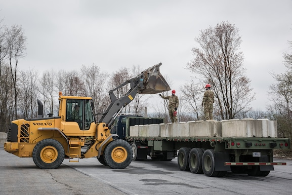 U.S. Airmen from the 201st RED HORSE Squadron, Pennsylvania Air National Guard, load retaining wall blocks on a wheel loader.