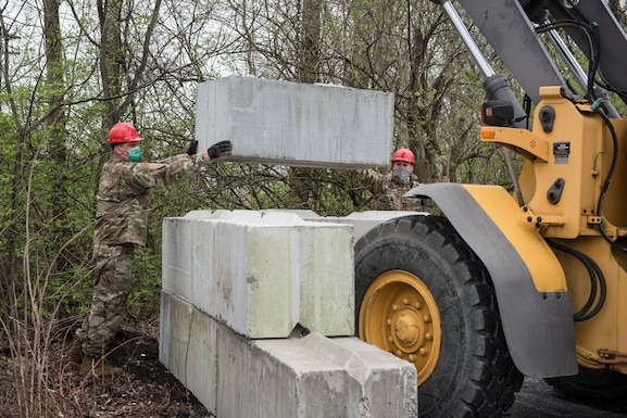 U.S. Air Force Staff Sgt. Peter Louden, left, and Senior Airman Randy Miller, pavements and construction Airmen with the 201st RED HORSE Squadron, Pennsylvania Air National Guard, maneuver a retaining wall block as it is lowered into place.