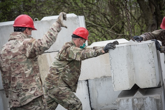U.S. Airmen with the 201st RED HORSE Squadron maneuver a retaining wall block as it is lowered into place.