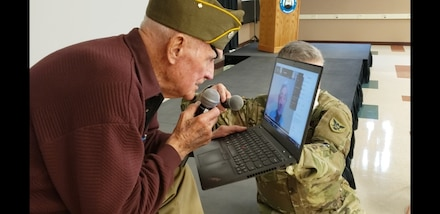 Tom Sitter, World War II veteran and Days of Remembrance speaker for the 86th Training Division is surprised with a teleconference meeting with a Dachau survivor, Elly Gotz, at Fort McCoy, Wis., April 9. Sitter was one of the Soldiers who liberated Dachau. (U.S. Army Reserve photo by Sgt. 1st Class Debralee Best/86th Training Division)