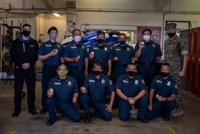 海兵隊太平洋基地司令官のウィリアム・バワーズ准将(右端)と記念撮影を撮る10人の日本人キャンプ・シュワ消防署員、2021年4月2日、消防署内