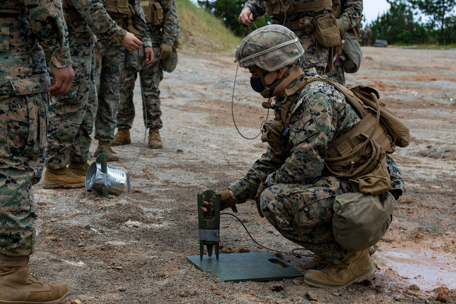 A U.S. Marine kneels while setting up an expedient shape charge as a group of Marines stand facing him, observing