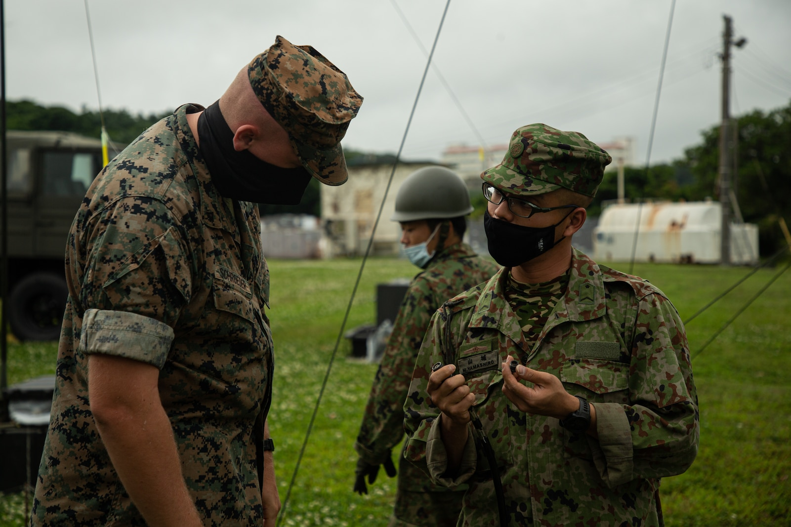 A U.S. Marine and a JGSDF soldier stand next to each other and discuss a piece of radio equipment held in the JGSDF member's hands in a grass field with military vehicles and equipment around them.