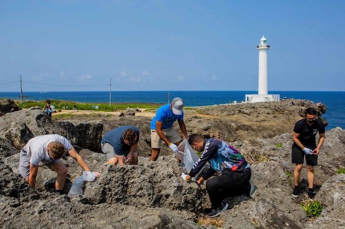 海兵隊基地の独身隊員の会に所属する隊員らが週末の休みを利用して残間岬を訪れ、残波岬灯台の見える周辺の岩場に隠れたゴミを拾い集めました、沖縄県読谷村残波岬、2021年3月20日