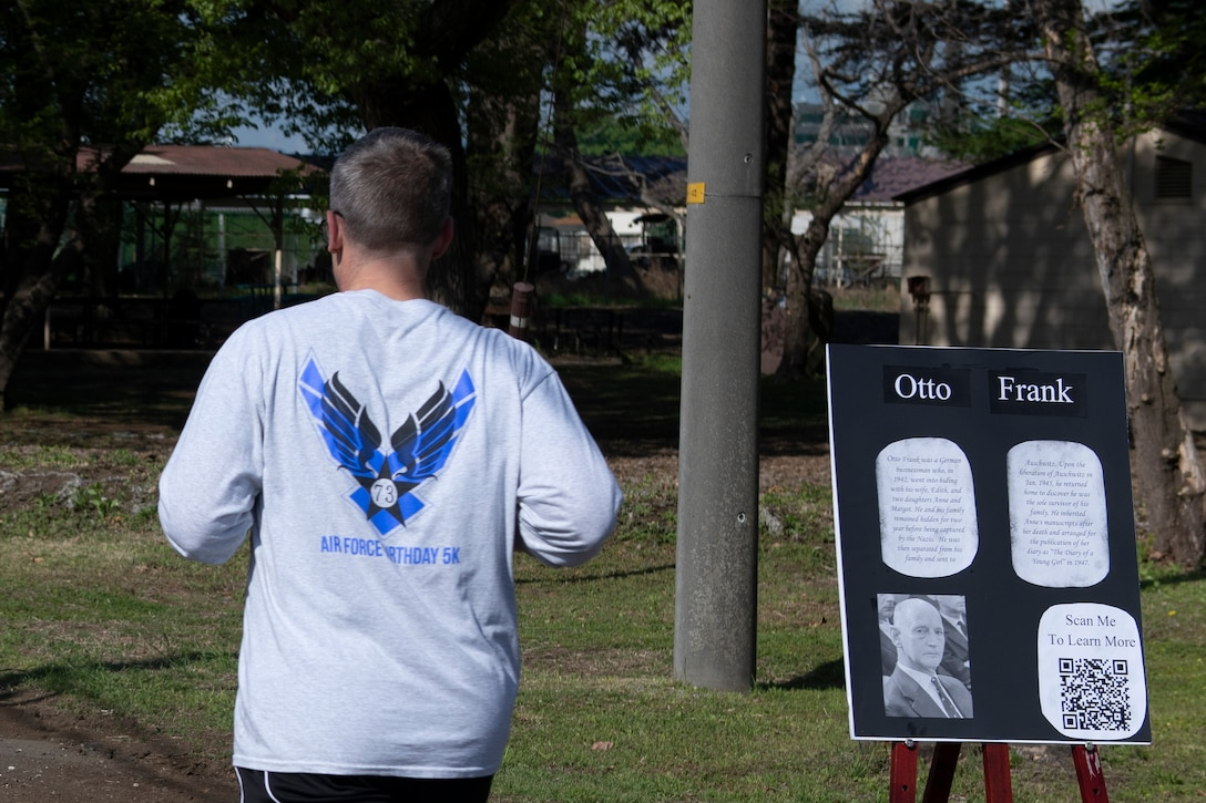 """A participant runs past Otto Frank's display board during the Holocaust Remembrance 5k and Walk near the Par 3 Golf Course on Yokota Air Base, Japan, April 9, 2021. Otto Frank was the sole surviving member of his family and later published the writings of his daughter in """"The Diary of Anne Frank."""" (U.S. Air Force photo by Staff Sgt. Joshua Edwards)"""