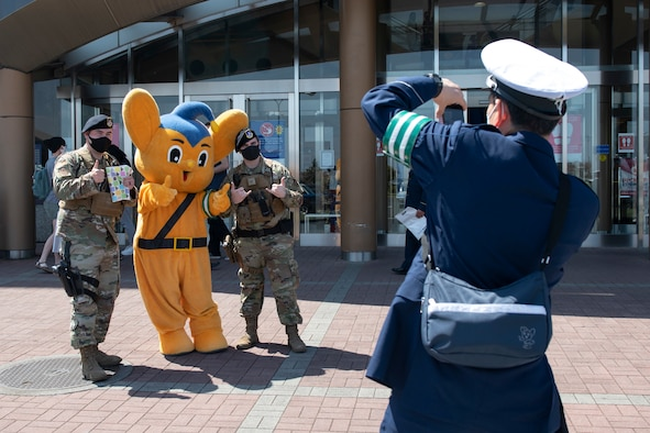 A Japanese National Police officer takes a photo of two 374th Security Forces Squadron members with Pipo-kun, JNP mascot, at the Yokota Community Center on Yokota Air Base, Japan, April 11, 2021. Pipo-kun posed for photos during a traffic safety campaign tailored to Yokota members. (U.S. Air Force photo by Staff Sgt. Joshua Edwards