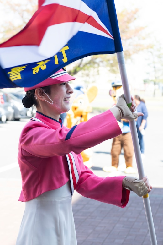A Japanese National Police Honor Guard member twirls at flag during a concert at the Yokota Community Center on Yokota Air Base, Japan, April 11, 2021. Along with the concert, the JNP also brought out a mascot and handed out information packets in an attempt to educate Yokota members on traffic safety. (U.S. Air Force photo by Staff Sgt. Joshua Edwards)