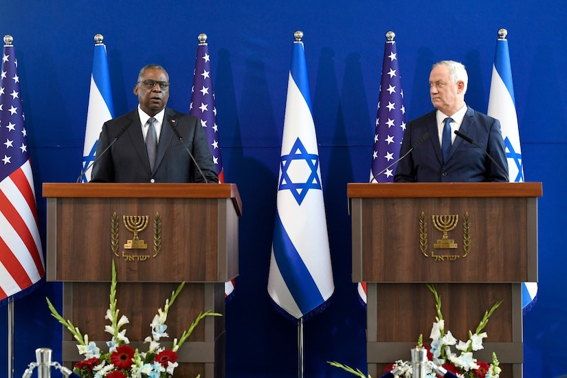 Two men stand on a podium and speak to reporters.