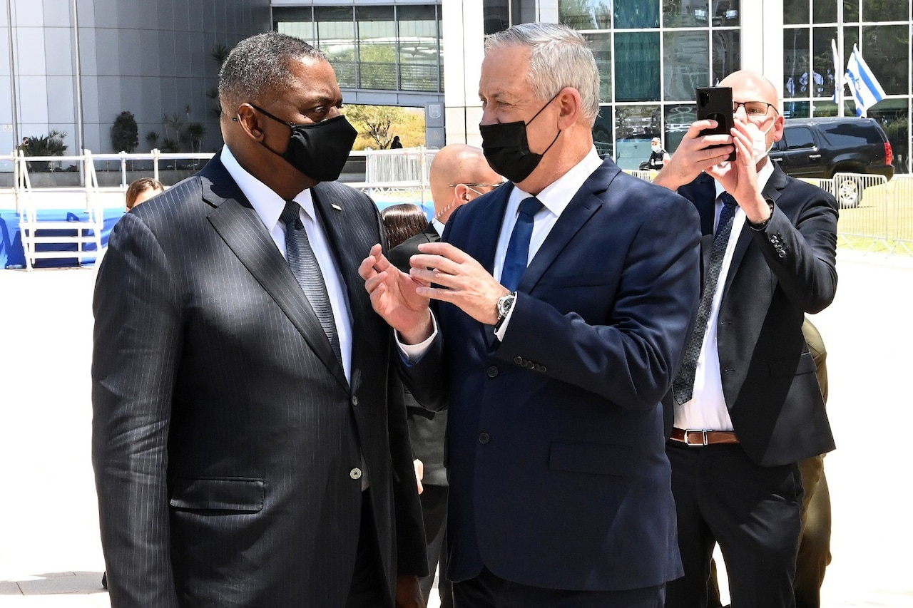 Two men wearing masks speak to each other while a third man takes a picture.