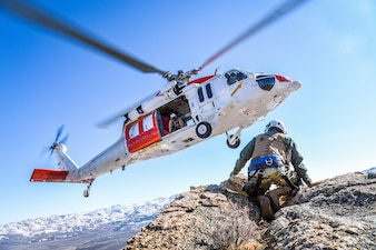 "An MH-60S Knighthawk helicopter assigned to the ""Longhorns"" of Helicopter Search and Rescue (SAR) Squadron, practices pinnacle landings and extractions during a mountain flying SAR training event."