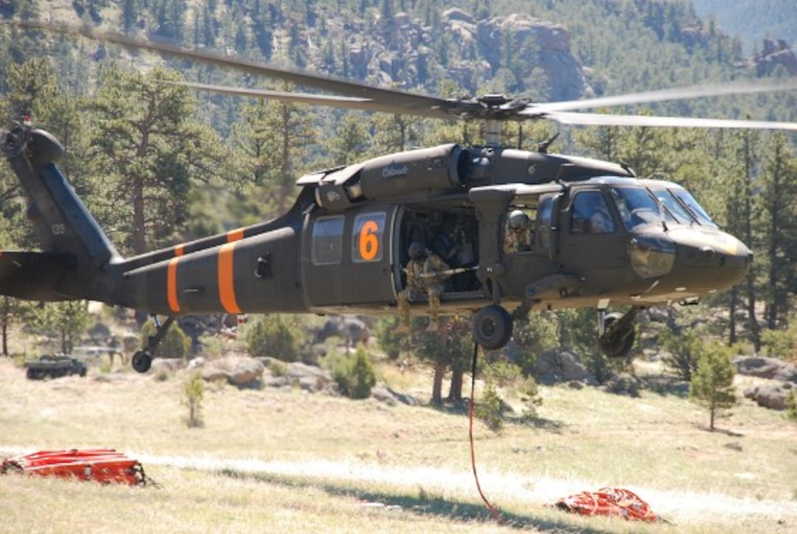 A Colorado Army National Guard Black Hawk helicopter, equipped with an aerial water bucket, departs from Button Rock Reservoir, Lyons, Colorado, to conduct bucket training in preparation for wildland fire season.