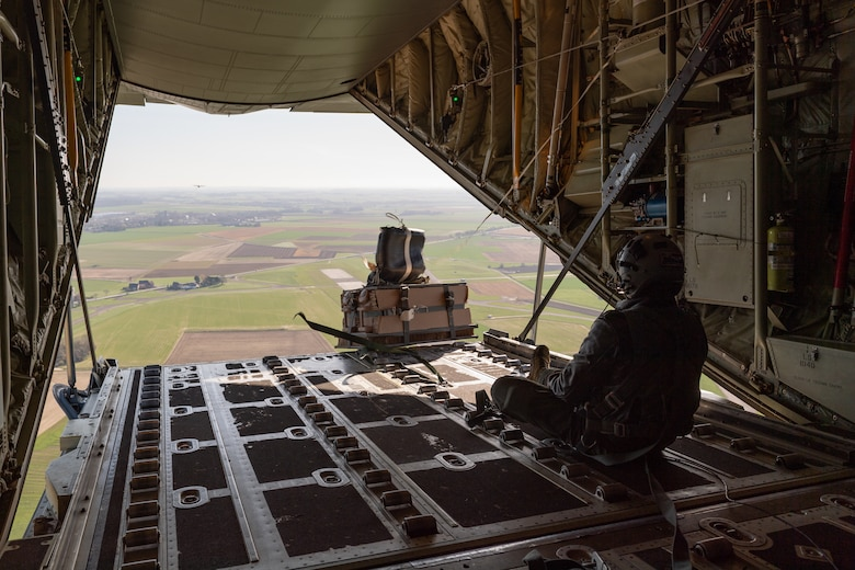 Airman sitting on an aircraft as cargo drops over edge.