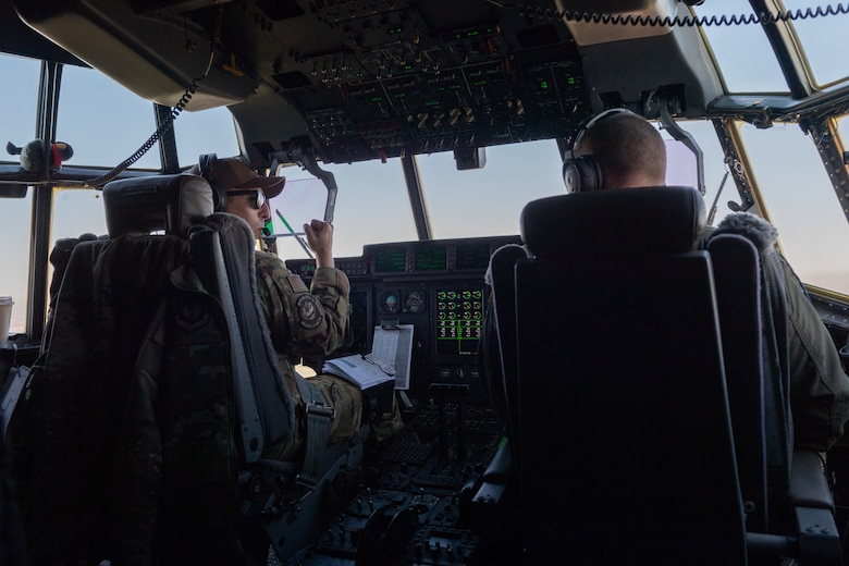 Pilots sitting in the cockpit of an aircraft.