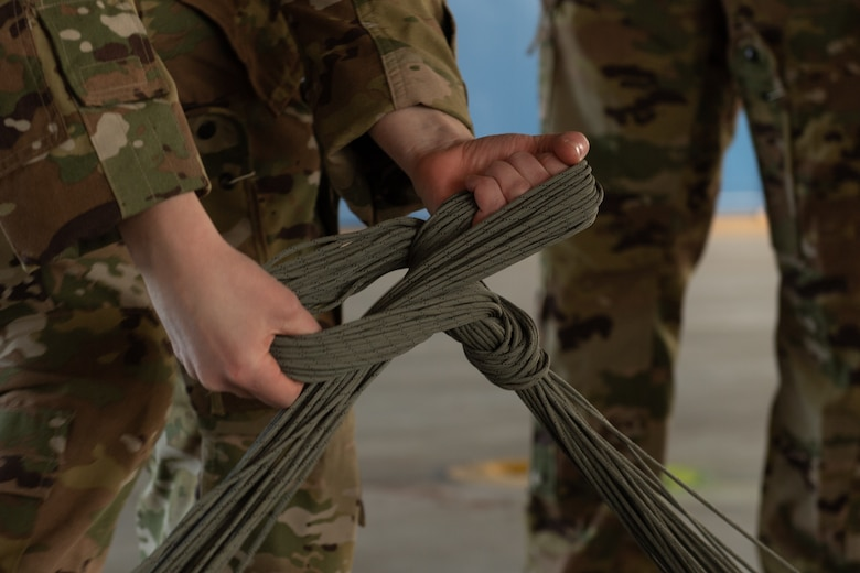 Close-up of hands holding a parachute line.