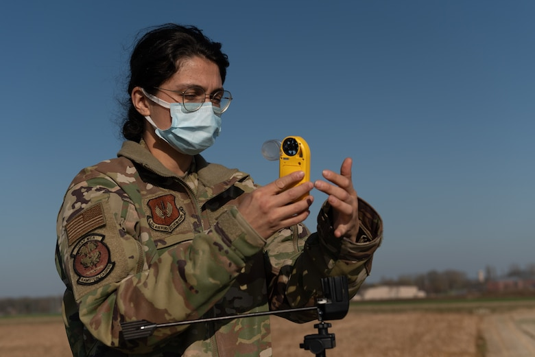 Airman holding wind measuring instrument.