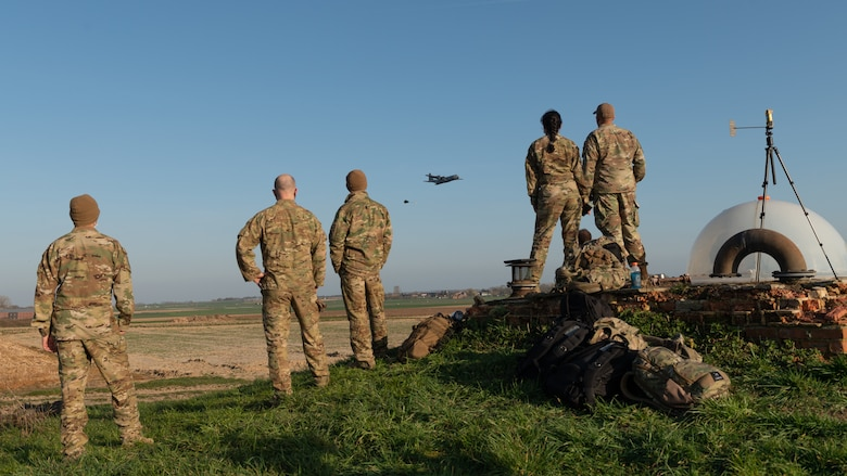 Airmen standing on a hill, looking at a plane in the distance.