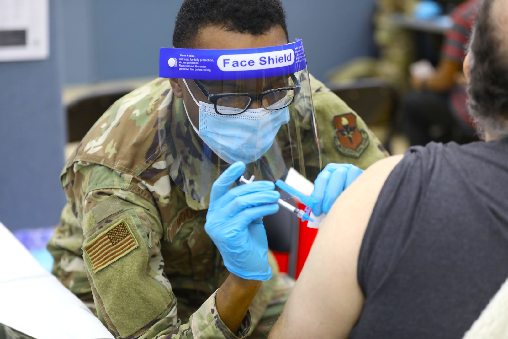 An Air Force medical technician administers the COVID-19 vaccine at a state-run, federally-supported COVID-19 Community Vaccination Center.