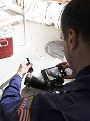 Chief Warrant Officer William Hockensmith, a marine inspector at Coast Guard Marine Safety Unit Portland, documents a damaged pipe during an inspection of the small passenger vessel Adventure Bound at a dry dock in Ilwaco, Washington, March 9, 2020. Small passenger vessels like the Adventure Bound that operate in saltwater routes are required to receive dry dock inspections every two years. (U.S. Coast Guard photo by Petty Officer 1st Class Levi Read)