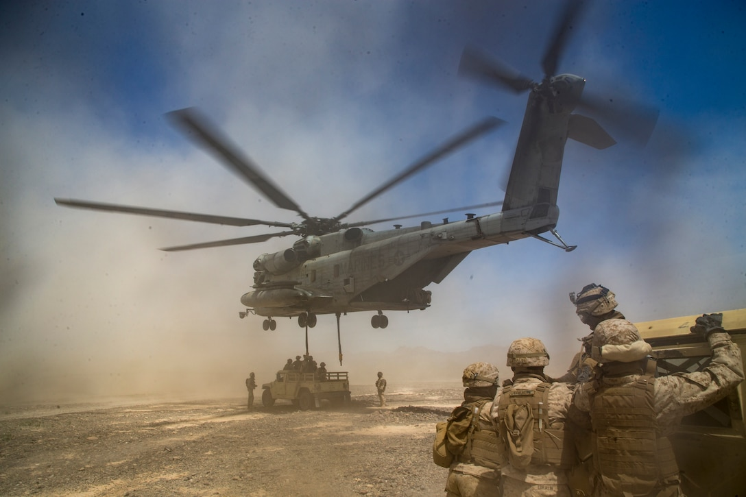 A large helicopter prepares to lift a humvee into the air.