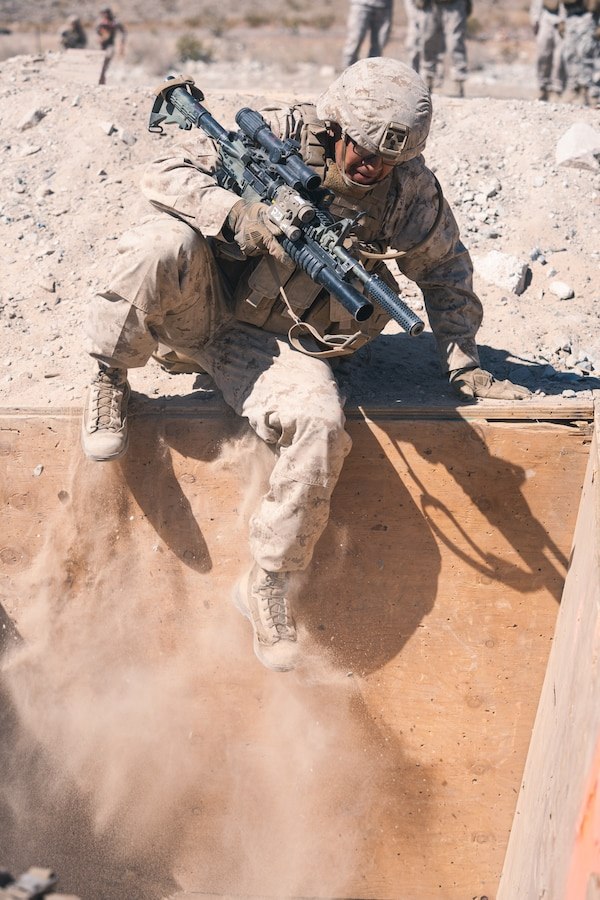 A U.S. Marine with Company B, 1st Battalion, 5th Marine Regiment, jumps into a trench during the Platoon Attacks at Range 410A while participating in Integrated Training Exercise (ITX), 3-21 at Marine Corps Air Ground Combat Center, Twentynine Palms, California, April 9, 2021. The purpose of ITX is to create a challenging, realistic training environment that produces combat-ready forces capable of operating as an integrated Marine Air Ground Task Force.  (U.S. Marine Corps photo by Lance Cpl. Andrew R. Bray)