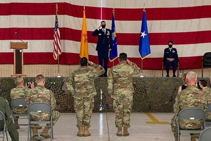 Col. Sefzik stands on the center of the stage holding a salute, with an American flag, New Mexico State flag, Air National Guard flag, and brigadier general one star flag behind him. on the floor two airmen salute Col. Sefzik as a crowd of soldiers and airmen watch