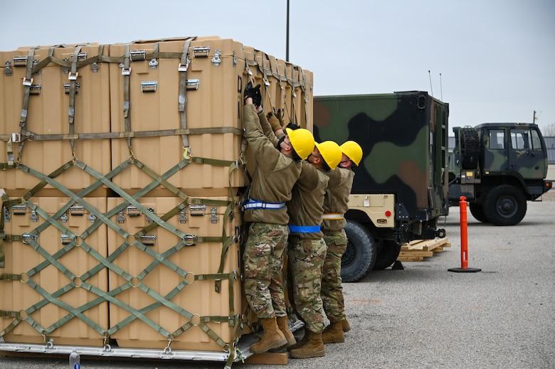 Three Airmen tightening the straps down on cargo sitting on a pallet.