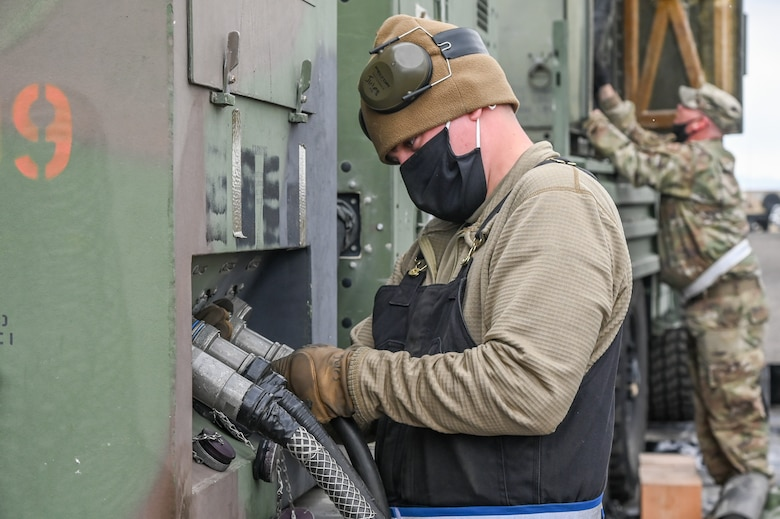 An Airman hooking up an electric cable to a generator.