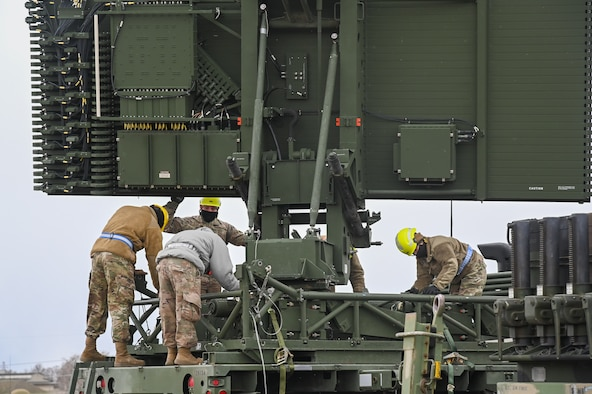Four Airmen working on a AN/TPS-75 radar system.