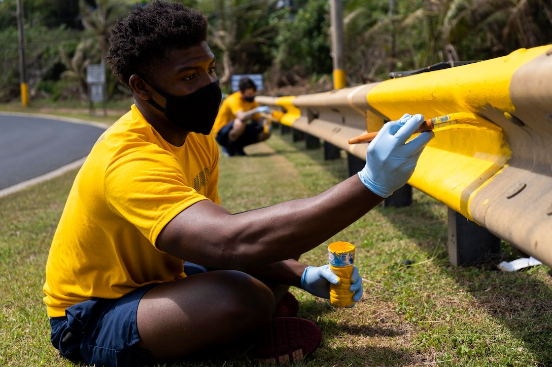 A sailor paints a guardrail yellow.