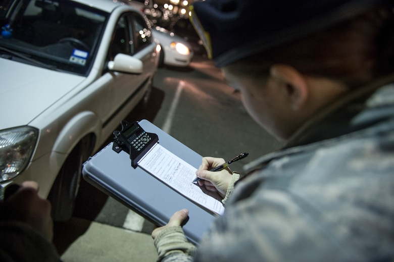 Airman 1st Class Kaitlyn Evans prepares a vehicle parking ticket during her night-shift duty at Joint Base Andrews, Maryland. Evans maintains proficiency while balancing her career and ownership of a horse with support from friends and family. She is an 11th Security Forces Squadron patrolman at Andrews Air Force Base, Maryland. (U.S. Air Force photo/Staff Sgt. Vernon Young Jr.)