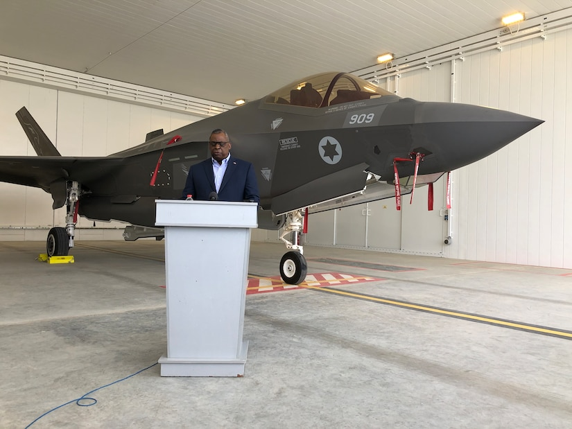 A man speaks at a podium in front of a 5th generation aircraft.