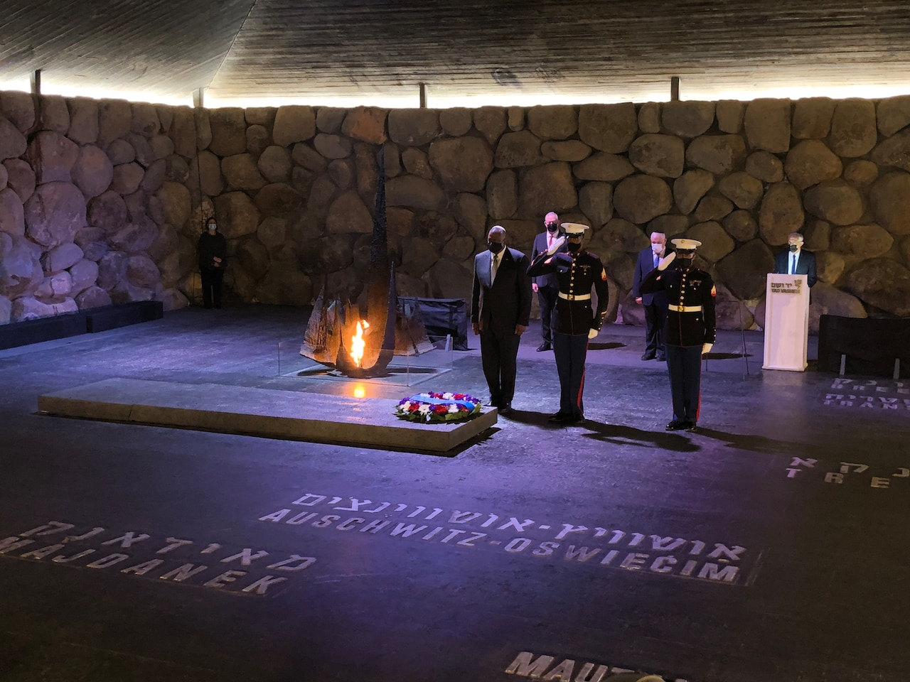 A man stands at attention next to two Marines after laying a wreath at the World Holocaust Remembrance Center.