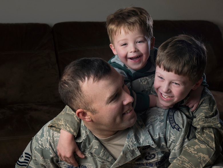 Master Sgt. Marc Richard, Det. 1, 66th Training Squadron, Arctic Survival School superintendent, smiles for a portrait with his sons Conner and Colton at their home in North Pole, Alaska. Although the Richard family is approaching their fifth deployment, they've kept their daily routine the same and will do what Richard and his wife, Paulle, have been doing for years -- press on. (U.S. Air Force photo/Staff Sgt. Vernon Young Jr.)