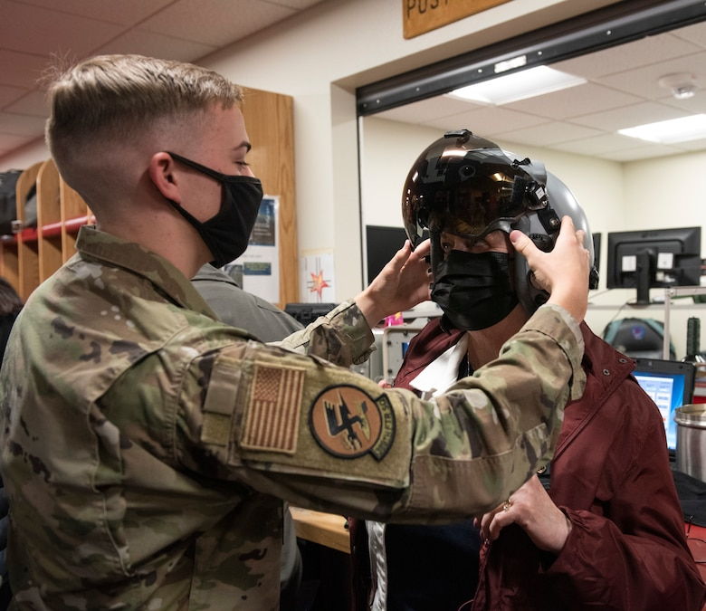 a male Airman is placing a pilots helmet onto a woman