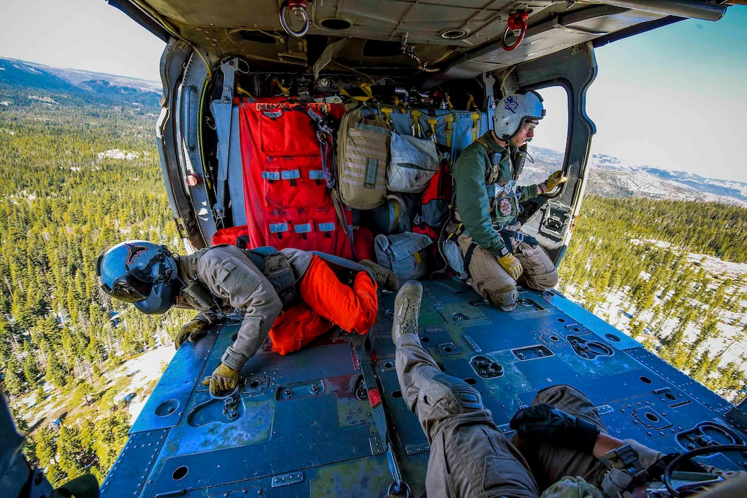 Sailors look over the side of two open helicopter doors as the helicopter flies over a mountain terrain.