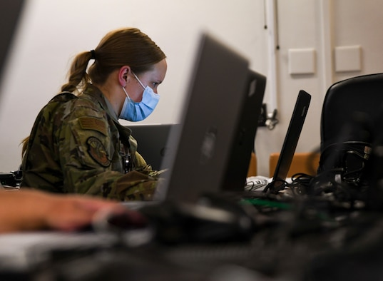 A photo of an airman sitting in front of a computer